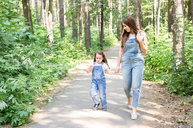 Семейная природа и люди концепции, мама и дочка проводят время вместе на прогулке в зелени