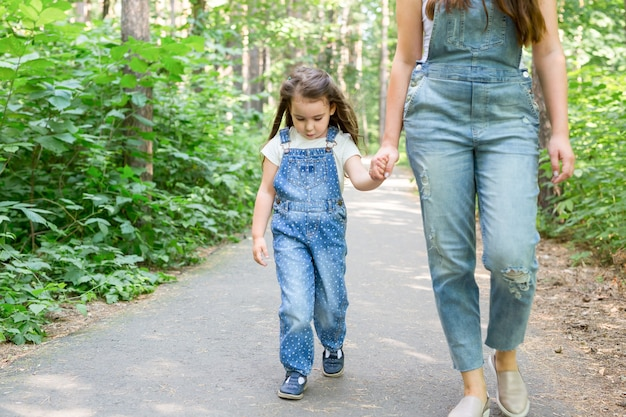 Family and nature concept - portrait of beautiful woman and child girl walking in summer park