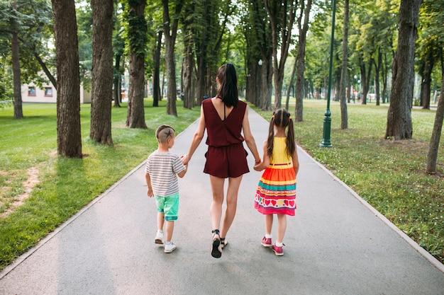 家族の自然公園のお出かけ。 2人の子供と一緒に歩く母親