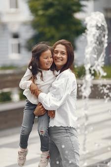 도시 분수 근처 가족. 물을 가지고 노는 교수형과 어머니입니다.