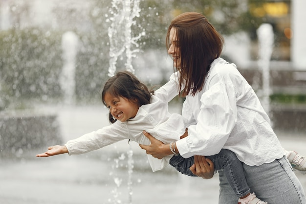 市の噴水の近くの家族。水で遊ぶ笑いを持つ母。