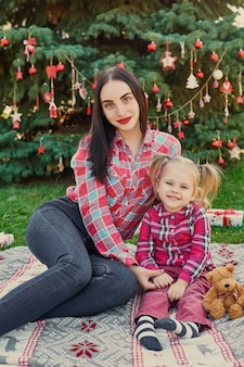 Family new year photo session of mother and daughter in july near the christmas tree with gifts in the park