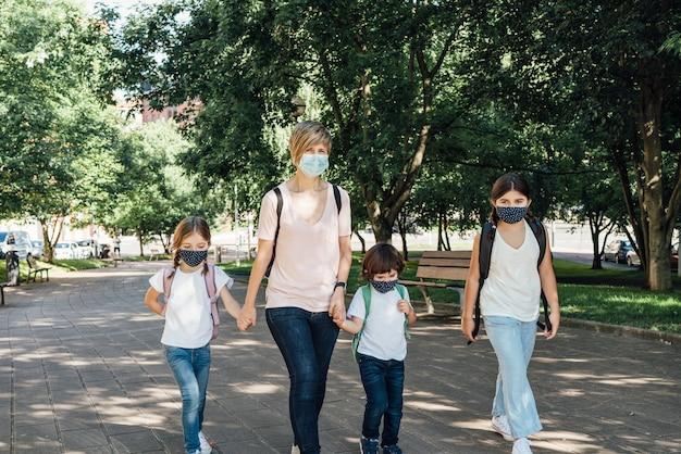 Covid19コロナウイルスのパンデミックのため、学年の初めにマスクを着用して学校に通う3人の白人の子供を持つ母親の家族