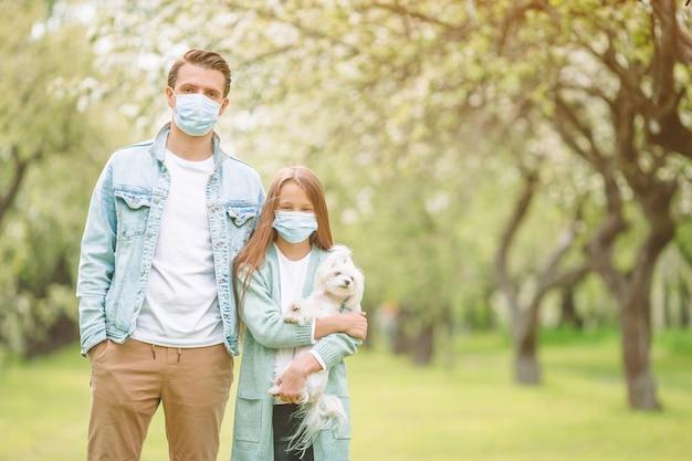 Семья отца и дочери в цветущем вишневом саду в масках