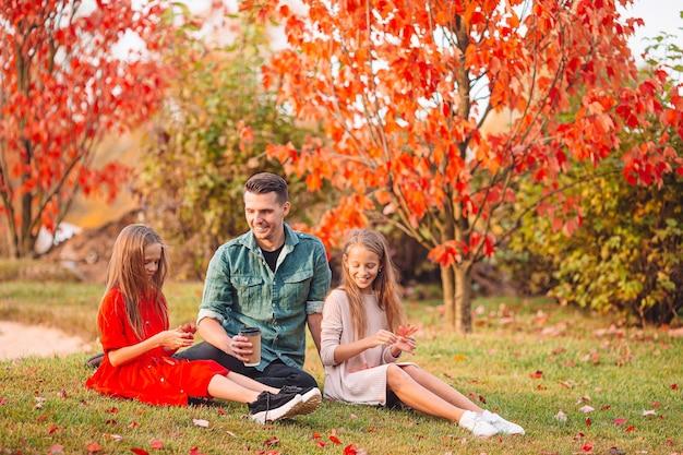 Семья отца и маленьких дочерей в прекрасный осенний день в парке