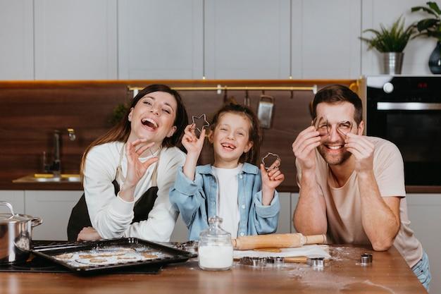 台所で料理をしている娘と父と母の家族