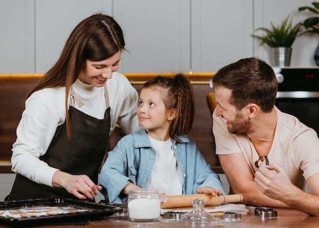 Семья отца и матери с дочерью готовит вместе на кухне