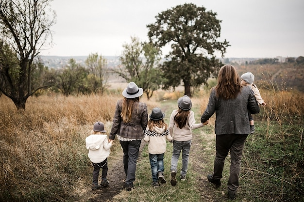 公園で一緒に歩いて、手を繋いでいる5人家族