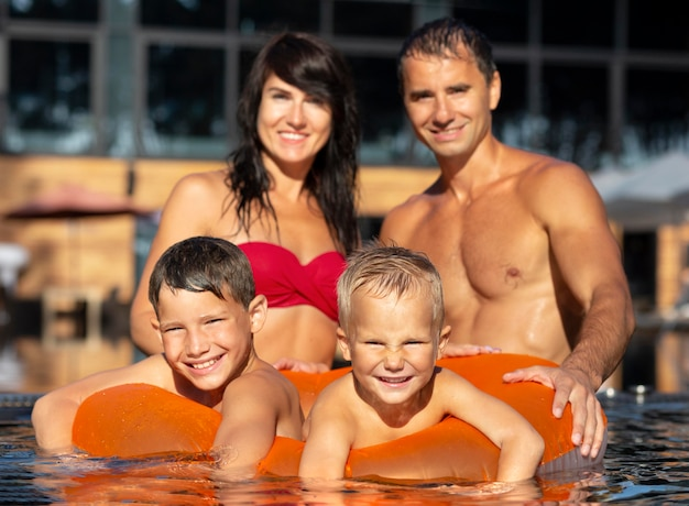 Семья из четырех человек, вместе наслаждаясь днем в бассейне
