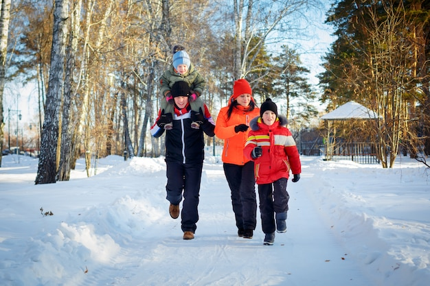 Семья из четырех человек наслаждается в зимнем парке