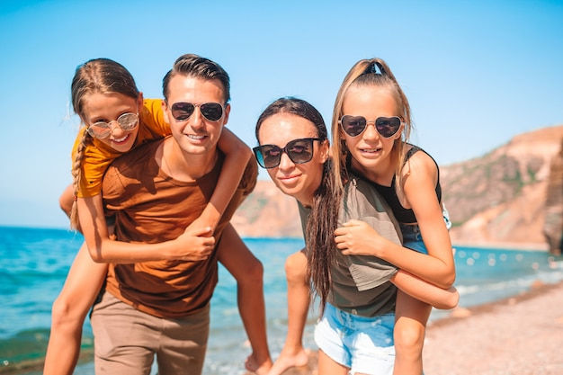 Семья из четырех человек, весело проводящих время на пляже
