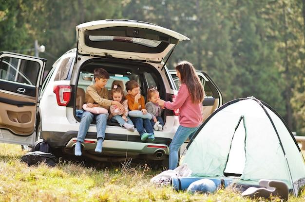車内の4人の子供と母親の家族。トランクに座っている子供たち。山の中を車で旅する、雰囲気のコンセプト。