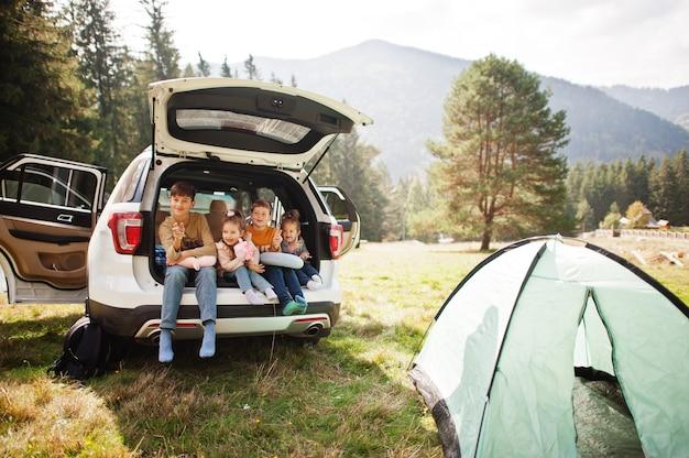 車内の4人の子供の家族。トランクに座っている子供たち。山の中を車で旅する、雰囲気のコンセプト。