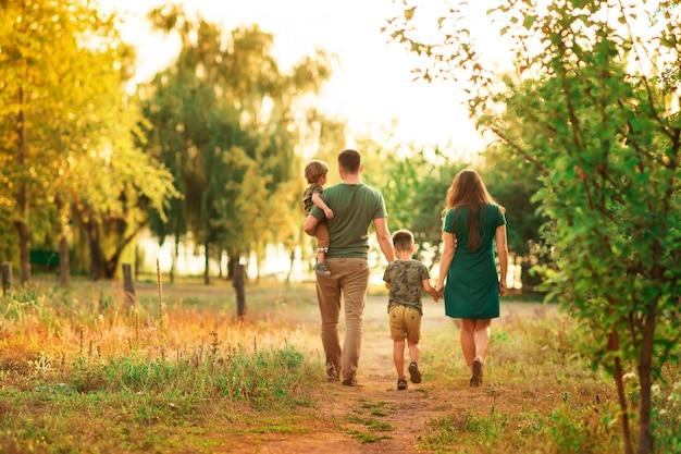 Семья из четырех человек, отец держит сына, родители держат руку ребенка на закате