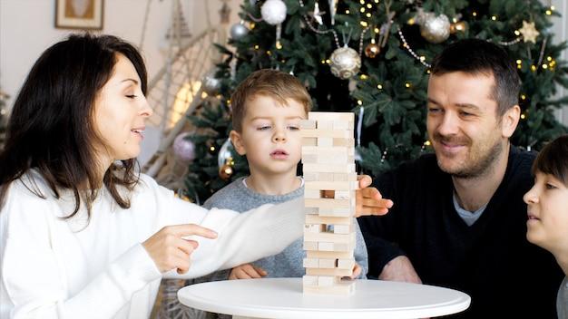 Семья из четырех человек вместе дома играет в настольную игру с деревянной башней.