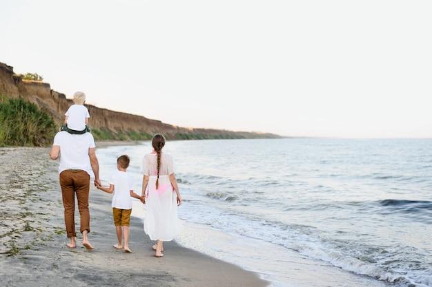 Семья из четырех человек гуляя вдоль берега моря. родители и двое сыновей. вид сзади