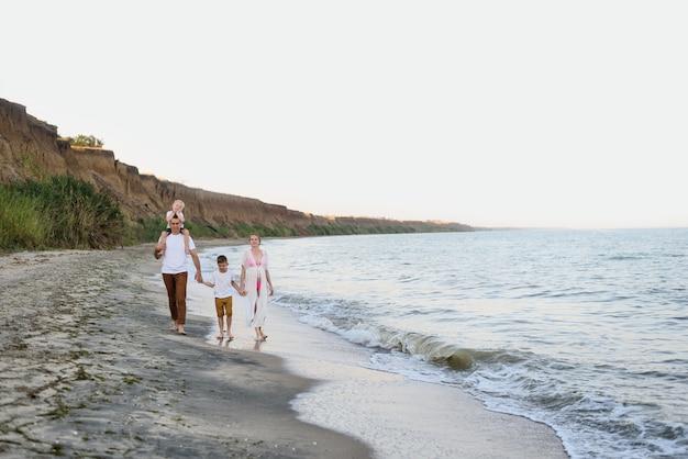 Семья из четырех человек гуляет по берегу моря, родители и двое сыновей, счастливая дружная семья