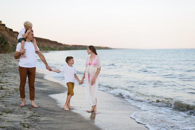 Семья из четырех человек гуляя вдоль берега моря. родители и двое сыновей. счастливая дружная семья