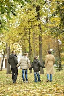 Семья из четырех человек гуляет вместе в осеннем лесу, вид сзади