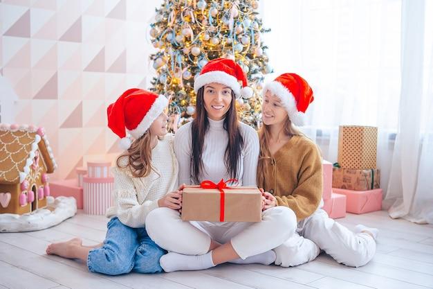 크리스마스에 선물을 가진 엄마와 아이들의 가족.
