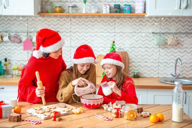 キッチンにクリスマスクッキーを持っているママと娘の家族