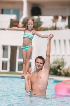 豪華なスイミングプールで夏休みを楽しんでいるママと小さな娘の家族