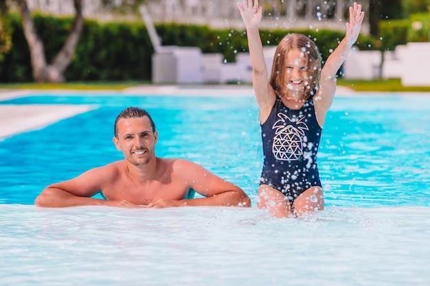 ママと小さなスイミングプールで夏休みを楽しんでいる小さな娘の家族