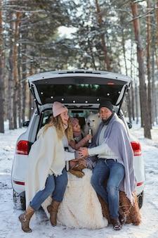 暖かいジャケットを着たママ、パパ、娘の家族と冬の森の車のトランクに座っている面白い白いサモエド犬。家族の幸せ、自然への配慮