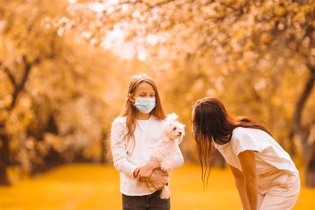 Семья матери и дочери в цветущем вишневом саду в масках