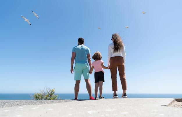 夏に手をつないで将来を見据えた母父と子少年の家族、背面図、生命保険。