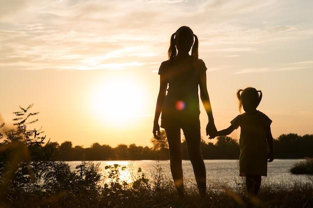 Семья родителей и детей силуэты на закате на открытом воздухе