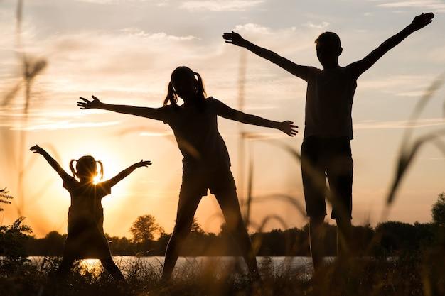 야외에서 일몰에 부모와 어린이 실루엣의 가족