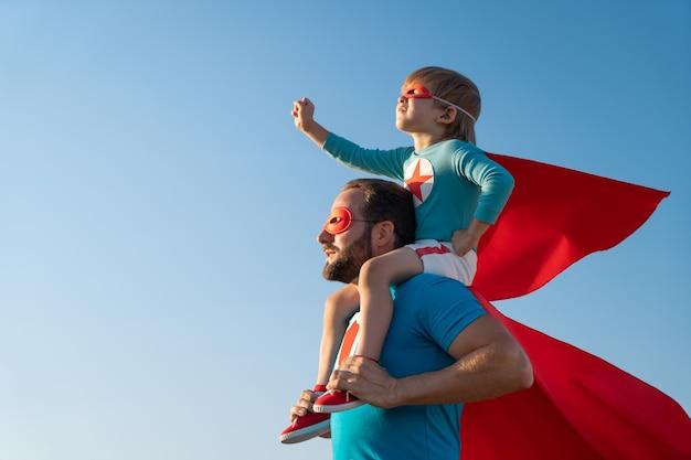 야외 재미 슈퍼 히어로의 가족입니다. 아버지와 아들이 푸른 여름 하늘 배경에 연주.