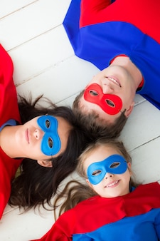 바닥에 누워 슈퍼 히어로의 가족입니다. 집에서 즐거운 시간을 보내는 행복한 가족