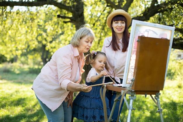 アウトドアの女性3世代家族。夏の自然の中で幸せな家族旅行。楽しいおばあさん、かわいいお母さん、かわいい女の子が、緑の公園のイーゼルで一緒に絵を描いています。