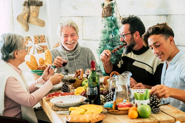 クリスマスの家を祝う間、ダイニングテーブルで一緒に夕食をとる3世代の家族