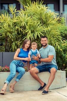 Семья из трех человек веселится и играет на открытом воздухе