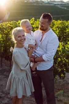 夏の日没時にブドウ畑に薄着の3人家族が立つ