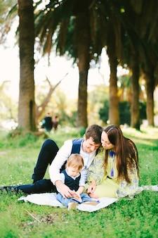 3人家族が晴れた日に公園でピクニックをしている
