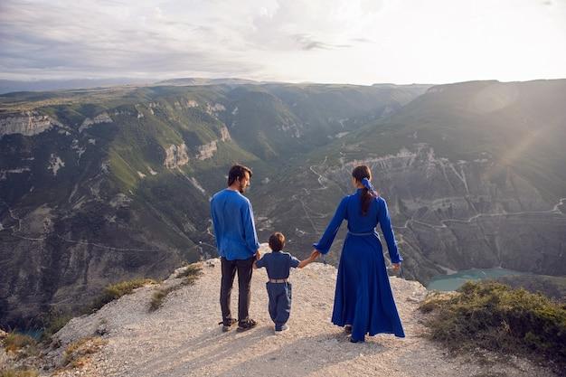 Семья из трех человек стоит в горном ущелье во время заката в дагестане