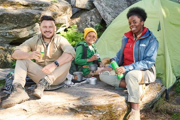 Семья из трех человек сидит возле палатки на открытом воздухе и пьет горячий чай во время кемпинга