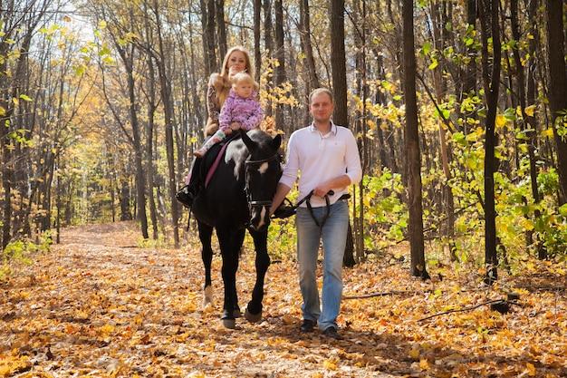 가을 숲에서 산책하는 말과 함께 세 가족