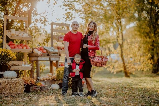 オープンマーケットの場所でポーズをとって妊娠中の母親と3人家族