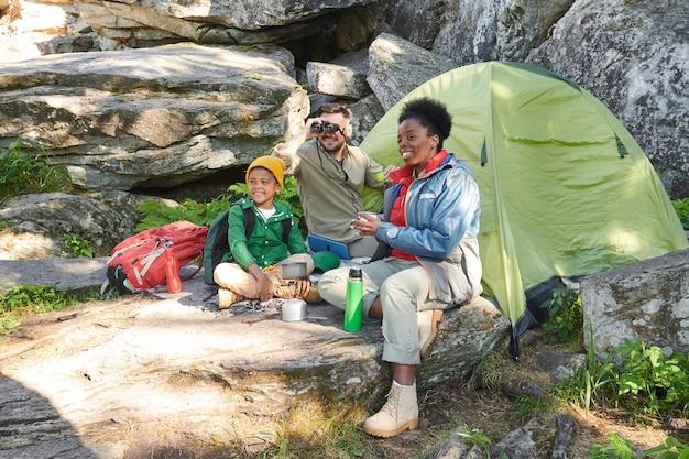 Семья туристов наслаждается дикой природой и пьет чай, сидя возле палатки на открытом воздухе.