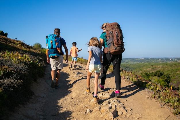 トラックを歩いているバックパックを持つ旅行者の家族。両親と2人の子供が屋外でハイキングします。背面図。アクティブなライフスタイルや冒険旅行のコンセプト