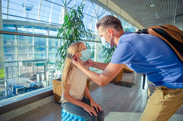 공항에서 얼굴 마스크에 두 가족. 아버지와 그의 딸은 코로나 바이러스와 독감이 발생하는 동안 안면 마스크를 착용합니다. 코로나 바이러스 및 그립으로부터 보호