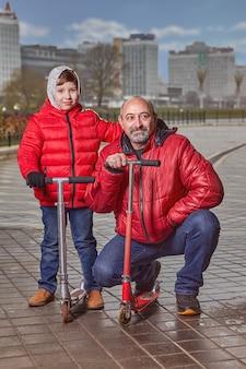 Семья из двух человек семи и пятидесяти лет идет по улице города в теплой одежде.