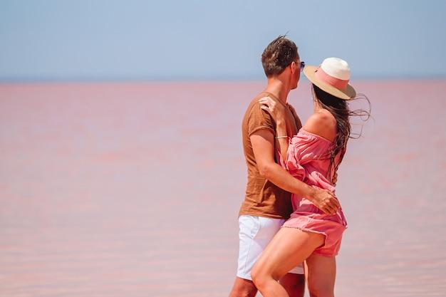 Семья на розовом соленом озере в солнечный летний день