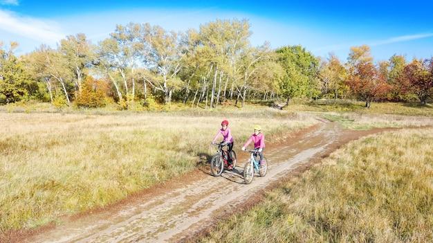 自転車に乗った家族秋の屋外サイクリング、アクティブな母と子の自転車