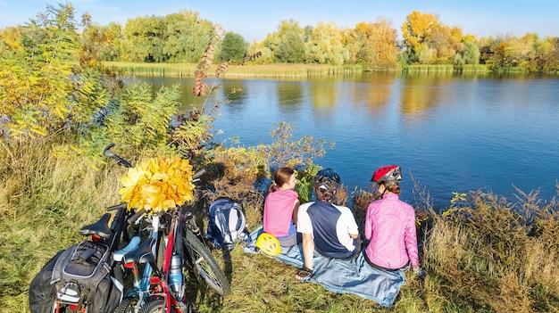 Семья на велосипедах осенью на велосипеде на открытом воздухе активные родители и ребенок на велосипедах